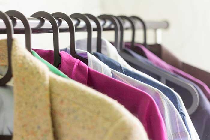 Shirts hanging up along a rack